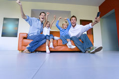 Family of four sitting on sofa cheering, arms raised, low angle view Royalty Free Stock Images