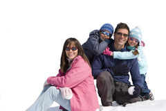 Family of four sitting together in snow field, smiling, portrait, cut out Royalty Free Stock Images