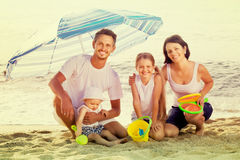 Family of four sitting together under beach umbrella on beach Royalty Free Stock Images