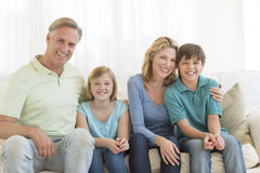 Family Of Four Smiling Together On Sofa Royalty Free Stock Photo