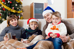 Family of four on sofa at home Royalty Free Stock Photos