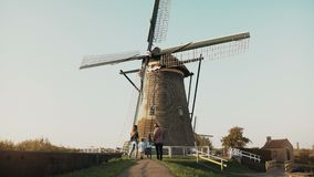 Family of four stand by huge old Dutch wind mill. Amazing shot of people before an architecture landmark. Back view. 4K. Family of four stand by huge stock footage