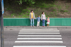 Family of four standing near crossover. Mother and father holds hand of little daughter and son and standing near crossover Stock Photo