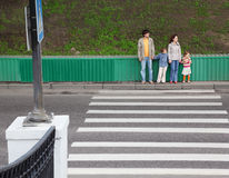 Family of four standing near pedestrian crossing. Mother and father holds hand of little daughter and son and standing near pedestrian crossing Stock Image