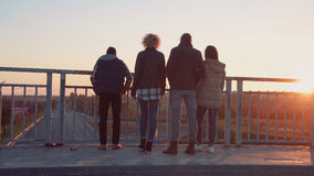 Family of four stands at barrier to observe nature. Family of four stands at barrier on bridge in city to observe nature as the sun sets beyond the tree line Royalty Free Stock Image