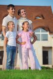 Family from four stands on grass against house stock photo