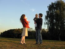 Family of four stay. Family stay on sundown at tree. father has different shoes royalty free stock photography