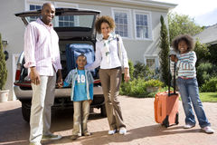 Family of four with suitcases by back of car, smiling, portrait, low angle view royalty free stock photography