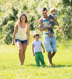 Family of four in sunny park Stock Photo