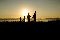 Family of four at sunset shadow black backlit Stock Photography