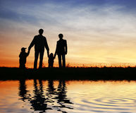 Family of four on sunset sky. Water Stock Images