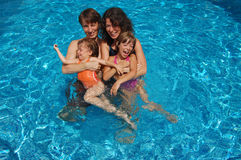 Family of four in swimming pool Stock Images