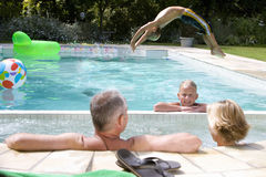 Family of four in swimming pool, boy (6-8) doing back flip into water, portrait of girl (8-10) smiling Stock Photography