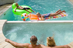Family of four in swimming pool, boy and girl (7-11) on inflatable chair and bed Stock Image