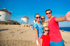Family of four taking selfie with a stick in front of windmills at popular tourist area on Mykonos island, Greece Stock Photos