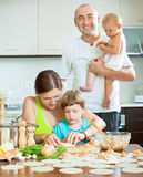 Family of four together in a cozy kitchen prepares food Royalty Free Stock Photos
