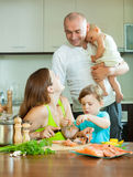 Family of four together in the kitchen prepares seafood Royalty Free Stock Images