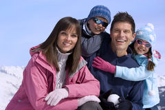 Family of four together in snow field, smiling, portrait, mountain range in background Royalty Free Stock Photo