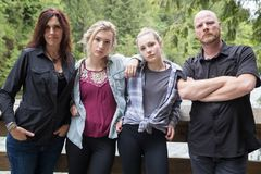 Serious family of four. Family of four with tough and serious expressions stock photo