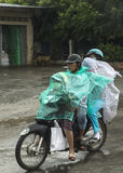 Family of four travel in the rain on motorbike. Stock Image