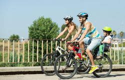 Family of four traveling by bicycles. Young smiling family with two little daughters traveling by bicycles. Focus on man Royalty Free Stock Image