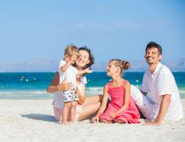 Family of four on tropical beach Royalty Free Stock Photo