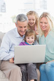 Family of four using laptop. Happy family of four using laptop at home Stock Images
