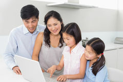 Family of four using laptop in kitchen. Family of four using laptop in the kitchen at home Royalty Free Stock Photography