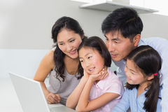 Family of four using laptop in kitchen. Family of four using laptop in the kitchen at home Royalty Free Stock Image