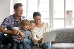 Family of four using laptop sitting on sofa at home. Young family of four bonding using laptop sitting on sofa at home, happy parents with adopted cute kids son stock photo