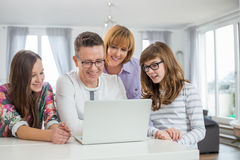 Family of four using laptop together at table in home Royalty Free Stock Photos