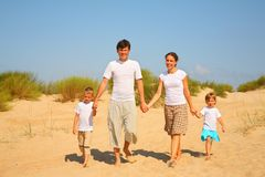Family of four walk on sand Royalty Free Stock Photos
