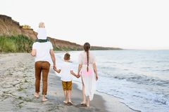 Family of four walking along the seashore. Parents and two sons. Back view stock photos