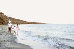 Family of four walking along the seashore. Parents and two sons. Back view stock photo