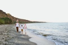 Family of four walking along the seashore. Parents and two sons. Happy friendly family stock photo