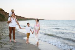 Family of four walking along the seashore. Parents and two sons. Happy friendly family stock photography