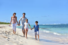 Family of four walking in the beach Stock Photos