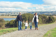 Family of four walking on beautiful trail in the hills Royalty Free Stock Photos