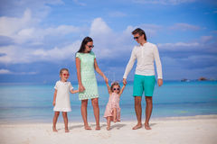 Family of four walking by the sea and enjoy beach Stock Images