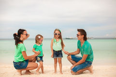 Family of four walking by the sea and enjoy beach Royalty Free Stock Photos