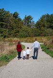 family of four walking on a trail Royalty Free Stock Images
