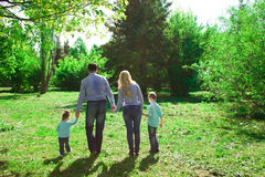A family of four walks in the park. Stock Image