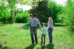 A family of four walks in the park. Royalty Free Stock Photos