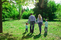 A family of four walks in the park. Stock Photo