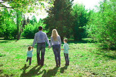 A family of four walks in the park. Royalty Free Stock Images