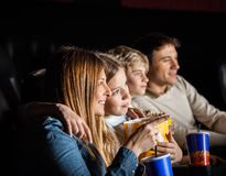 Family Of Four Watching Movie In Theater. Family of four having snacks while watching movie in cinema theater Royalty Free Stock Images
