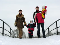 Family of four on winter bridge. Snow Stock Images