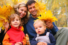 Family of four with yellow maple leaves. In wood in autumn Royalty Free Stock Images
