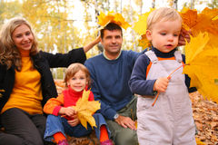 Family of four with yellow maple leaves in wood. In autumn Royalty Free Stock Image