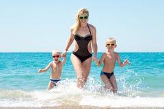 美丽的握手的母亲和两可爱的儿子运行在波浪 乐趣,family-friendly暑假 库存图片